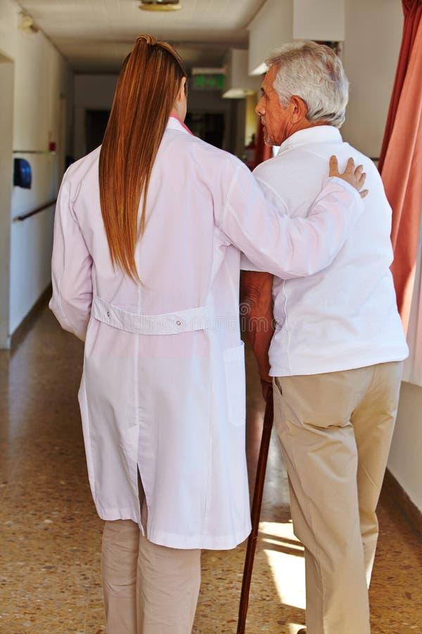 Pielęgnuje pomaga starszego pacjenta obrazy royalty free