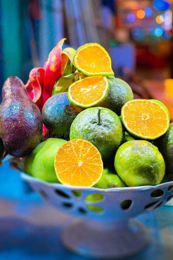 Piel of Asian exotic fruits on the plate. Apples, oranges, mangos, dragon and passion fruits royalty free stock images