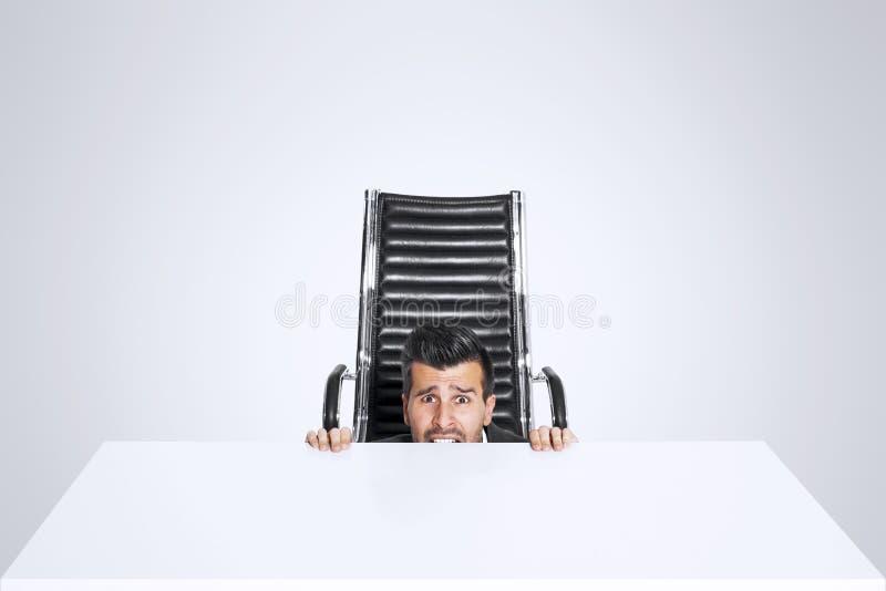 Piel asustada misma del hombre de negocios debajo del escritorio de oficina fotos de archivo libres de regalías