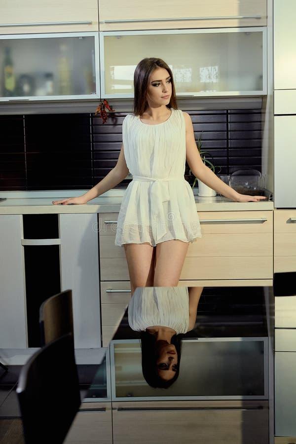 Piel blanca joven sonriente alegre femenina con el pelo moreno largo que presenta en la cocina foto de archivo libre de regalías