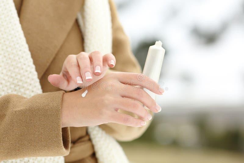 Piel de hidratación de la mano de la mujer que aplica la crema en invierno imagen de archivo libre de regalías