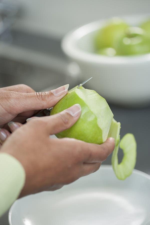Piel de la peladura apagado de una manzana verde usando un cuchillo de pelado imágenes de archivo libres de regalías