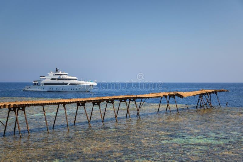 Piel de madeira longo que conduz no mar imagem de stock
