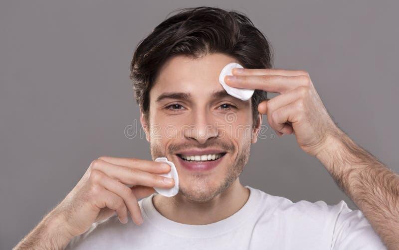 Piel hermosa de la cara de la limpieza del hombre con los cojines de algodón fotografía de archivo