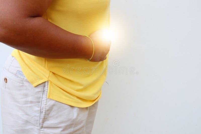 Piel masculina asiática, piel oscura, forma gorda, sosteniéndose en el área del vientre debido a la enfermedad, dolor de estómago fotografía de archivo libre de regalías