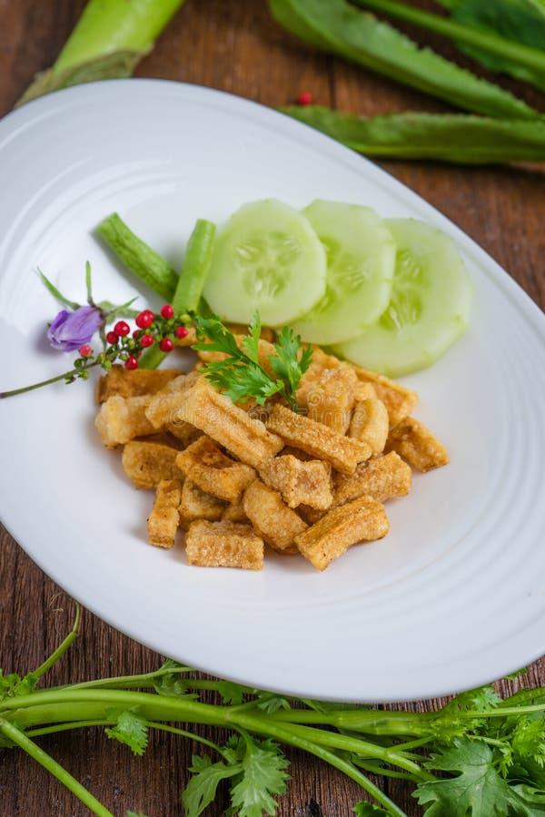 Piel seca frita del búfalo en la tabla de madera, comida tailandesa foto de archivo