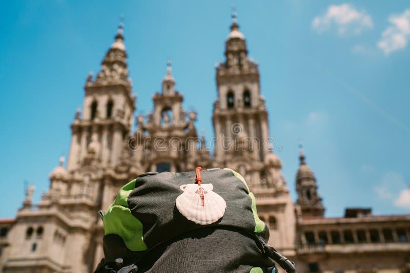 Pielgrzyma plecak z sławną pielgrzym maskotką i znaka seashell z krzyżem Saint James na przy Obradeiro kwadrata placem obraz stock