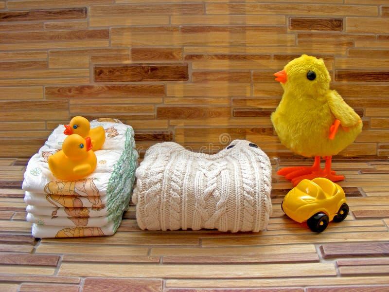 Pieluszki zabawka ustawia dla dziecka, brogujący pieluszki na bambusowym tle z żółtą kaczki zabawką fotografia royalty free