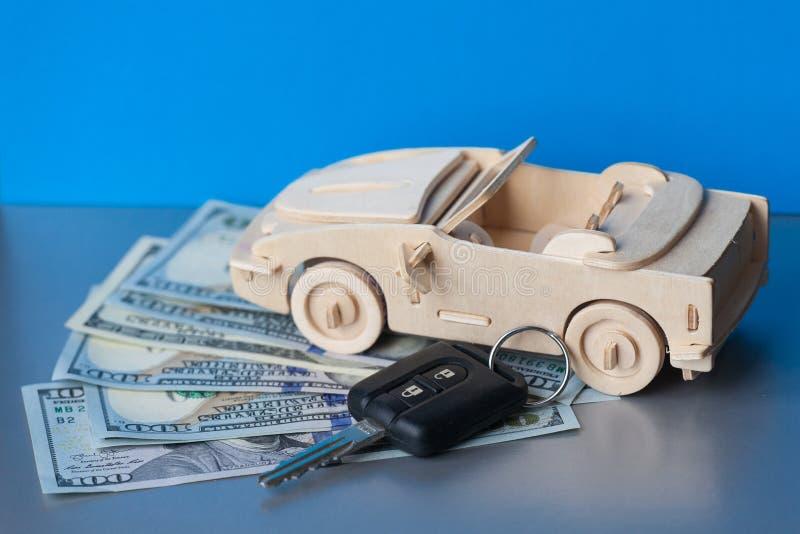 Pieniądze, Drewniany Zabawkarski samochód i klucza pojazd na błękitnym tle, zdjęcia royalty free