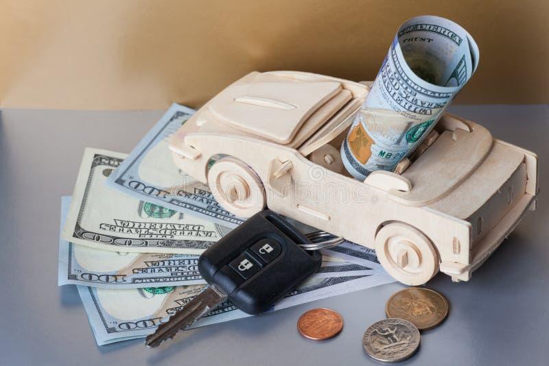 Pieniądze, Drewniany Zabawkarski samochód i klucza pojazd na Srebnym tle, obraz royalty free