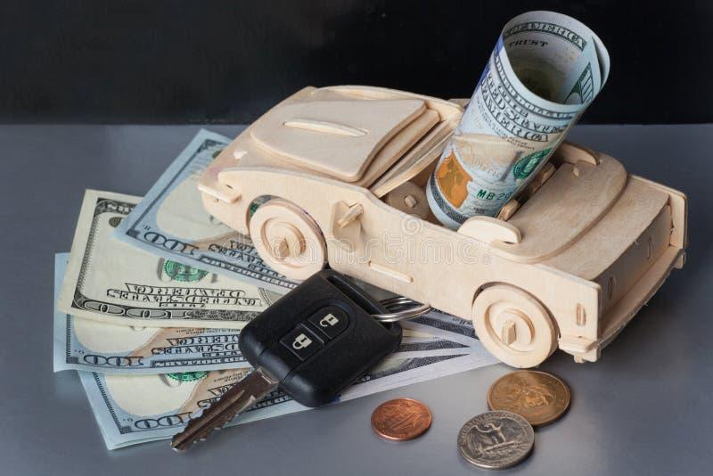 Pieniądze, Drewniany Zabawkarski samochód i klucza pojazd na Srebnym tle, fotografia royalty free