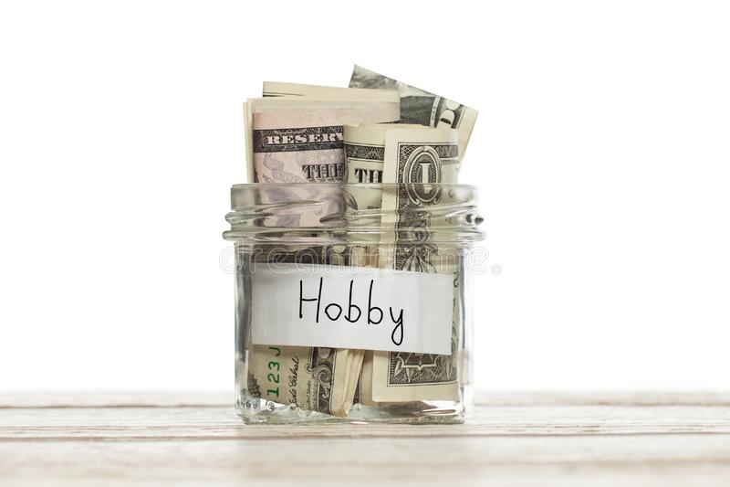 Pieniądze dla hobby Ratujący słój z dolarem amerykańskim dla hobby na drewnianej desce odizolowywającej obrazy stock