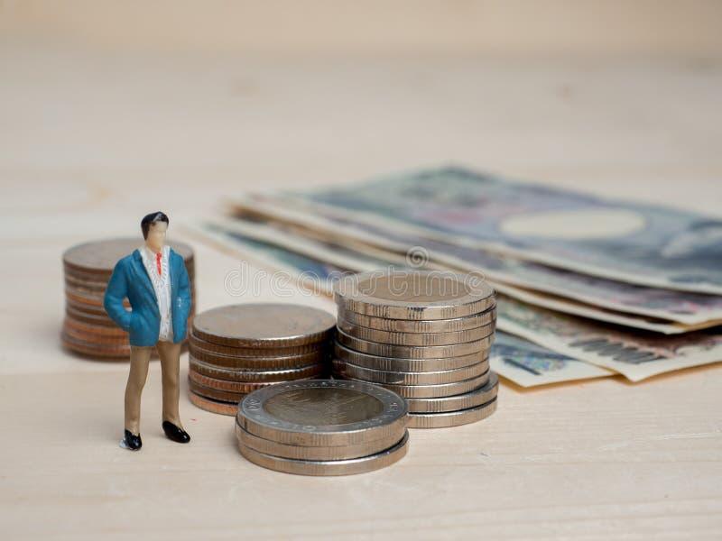 Pieniądze i biznesu pojęcie Biznesmen postaci mała pozycja zdjęcia stock