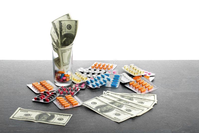 Pieniądze i leki odizolowywający na białym tle Zakończenie rozsypisko kolorowe pastylki, kapsuły, pigułki obok dolara zdjęcie royalty free