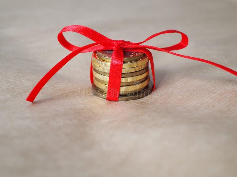 Pieniądze jako boże narodzenie prezent, monety na stole z czerwonym łękiem zdjęcia stock