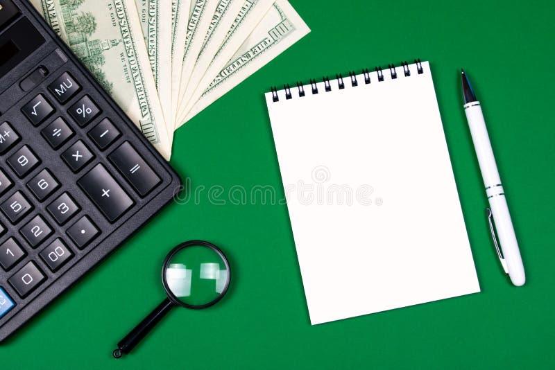 Pieniądze, kalkulator i notatnik na zielonym tle, obrazy royalty free