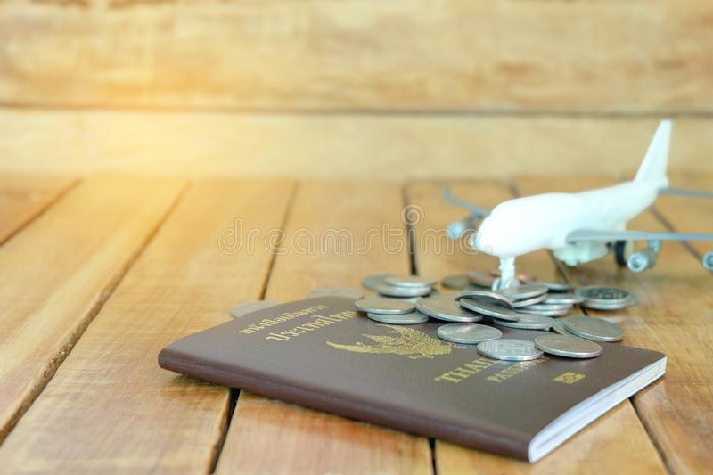 Pieniądze oszczędzania pojęcie dla wakacje z monety stertą, paszportem i samolot zabawką na drewnianych tło, fotografia stock