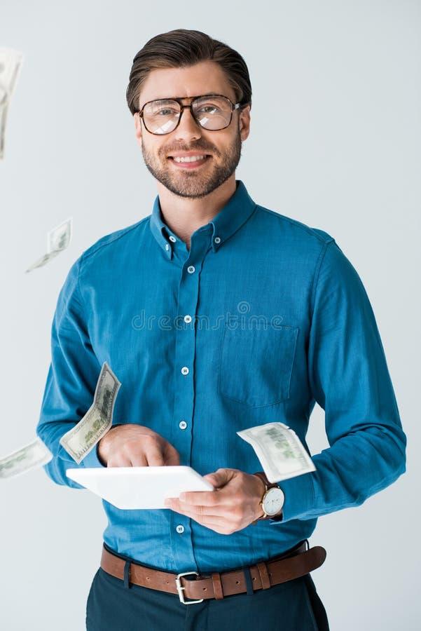 pieniądze spada wokoło młodego człowieka z pastylką fotografia royalty free
