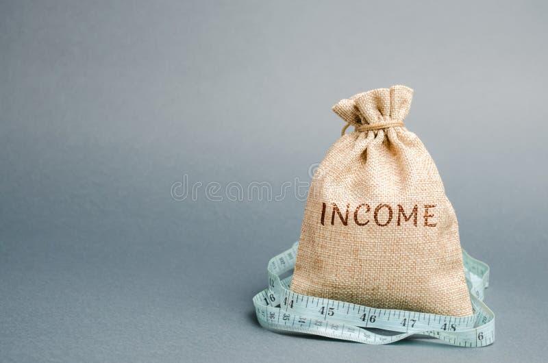 Pieniądze torba z słowo dochodem pomiarową taśmą i Obni?ony doch?d i zyski Obni?ony bud?et Strata pieni?dze niepomy?lny obrazy stock