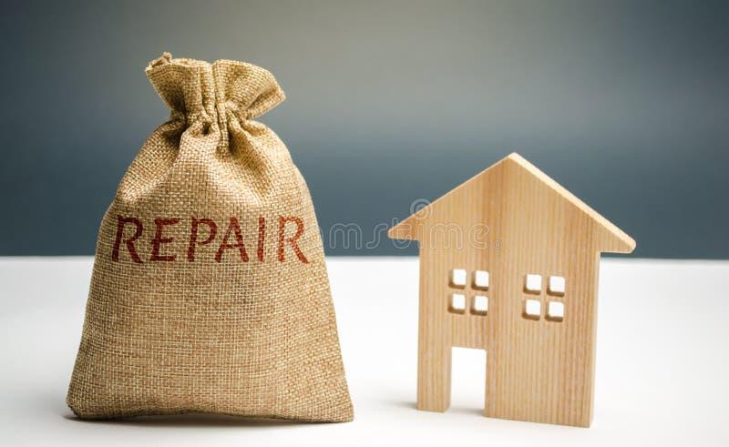 Pieniądze torba z słowo naprawą i drewnianym domem Oszczędzanie i akumulacja pieniądze naprawiać Pojęcie nowy dom, mieszkanie fotografia stock