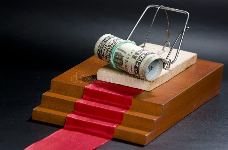 Pieniądze w mousetrap na czarnym tle i czerwonym chodniku obraz stock