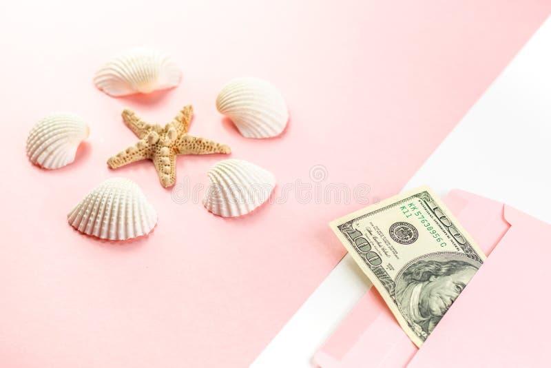 Pieniądze w różowej kopercie, rozgwiazda, seashells na błękitnym tle Podr?? bud?et Odbitkowa przestrze?, odg?rny widok zdjęcia stock