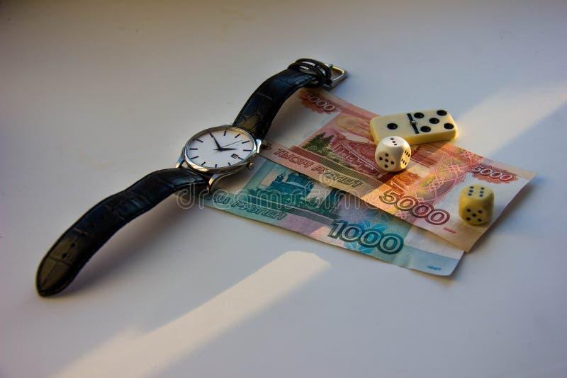 Pieniądze, zegarek, kostka do gry i domino, Promień światło spada na pieniądze rublu, kostka do gry, zegarek, domino obraz royalty free