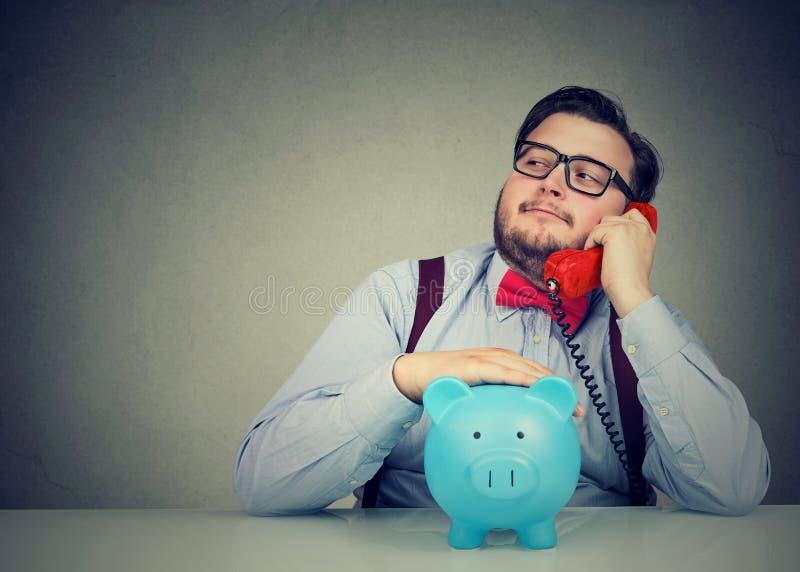 Pieniężny advisor z prosiątko bankiem callling na telefonie obrazy royalty free