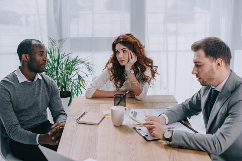 Pieniężny doradca robi obliczeniu podczas gdy partnerów biznesowych siedzieć fotografia royalty free