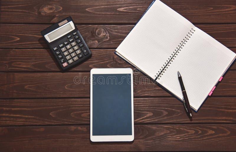 Pieniężny pojęcie, pastylka komputer osobisty, kalkulator, notepad na drewnianym tle, planistyczny dochód osobisty R?ka pisa? na  zdjęcie royalty free