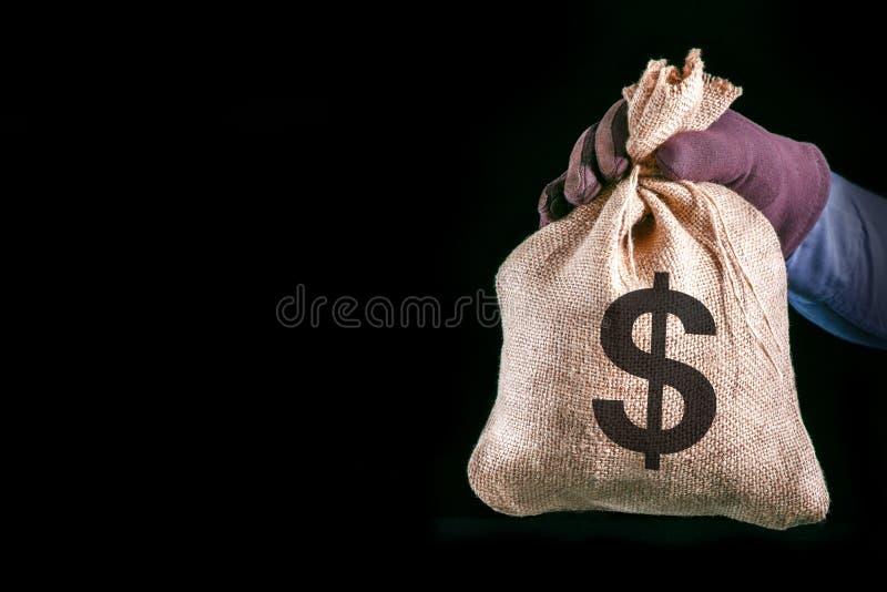 Pieni?dze torba z dolara ameryka?skiego znakiem Mężczyzna ręka z pieniądze torbą na czarnym tle z kopii przestrzenią Przest?pca o obraz royalty free