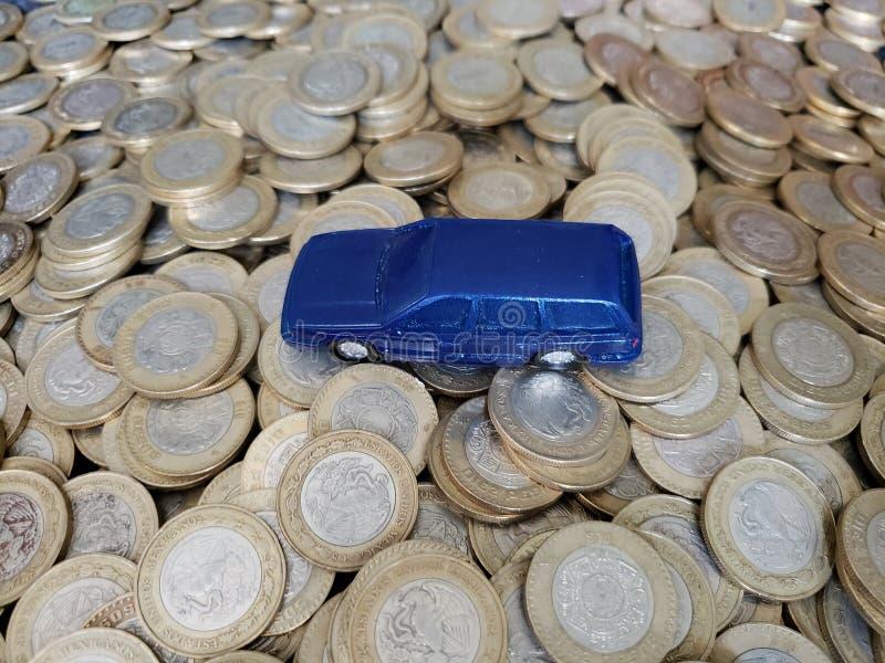 pieni?dze w automobilowym przemysle, posta? b??kitny samoch?d i monety dziesi?? meksyka?skich peso, zdjęcie stock