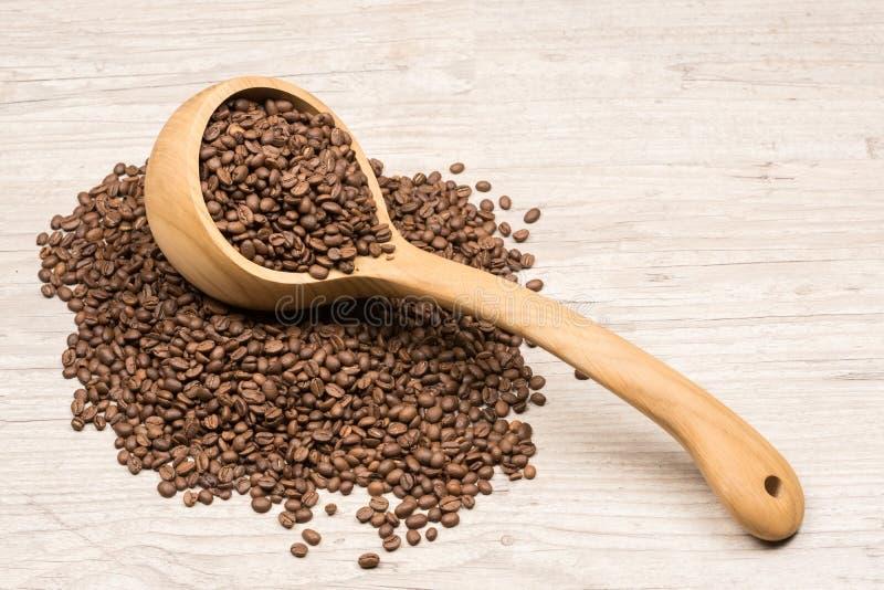 In pieno della siviera di legno dei chicchi di caffè che si trova sui chicchi di caffè arrostiti fotografia stock libera da diritti