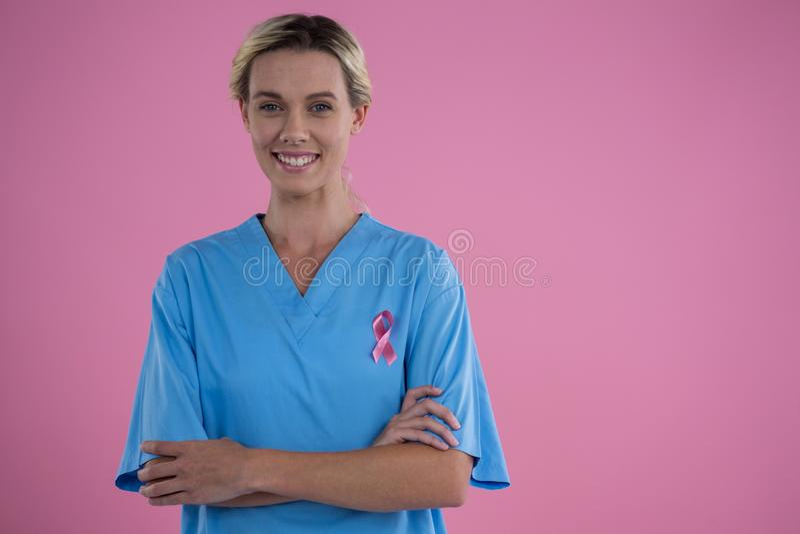 Piense el texto y la mano del control de la mirada que sostienen la tarjeta con las mujeres rosadas de la conciencia del cáncer d imagenes de archivo