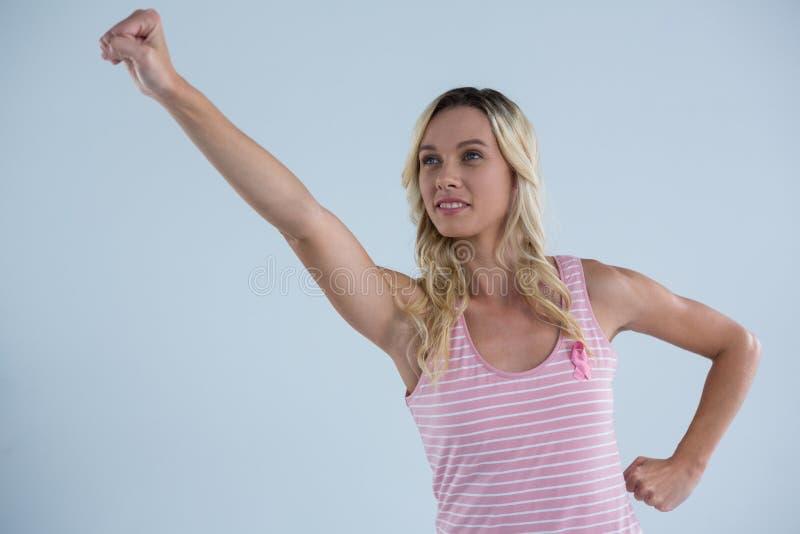 Piense el texto y la mano del control de la mirada que sostienen la tarjeta con la mujer rosada de la conciencia del cáncer de pe fotos de archivo libres de regalías
