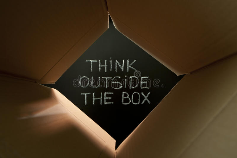 Piense fuera de la caja en la pizarra imagenes de archivo