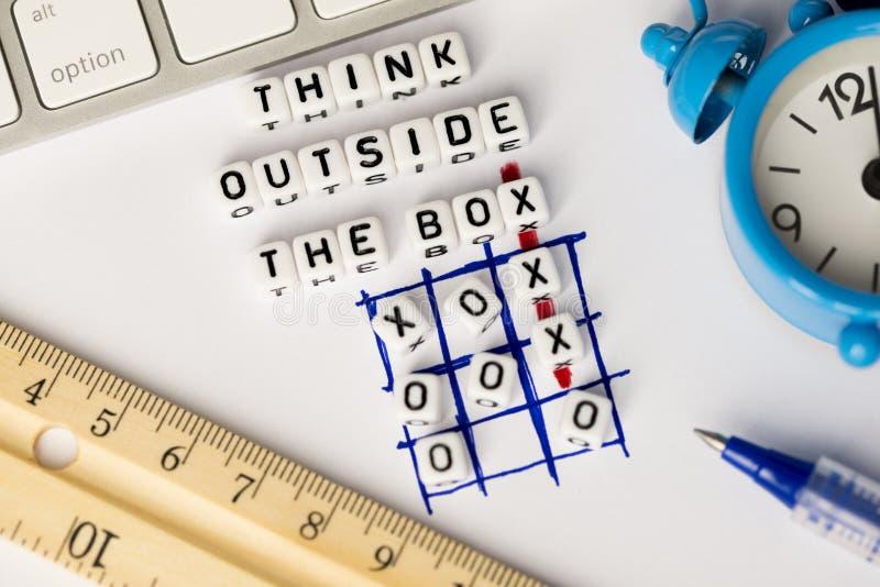 Piense fuera del consejo de la caja escrito con las letras plásticas en juego del tic-TAC-dedo del pie fotografía de archivo