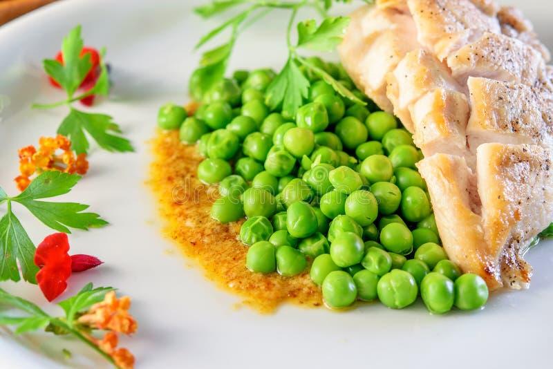 Pierś kurczaka smażony z brojonym zielonym grochem na białym zdobionym daniu zamykającym obraz stock