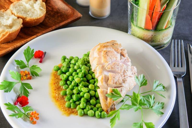 Pierś kurczaka smażony z zielonym groszkiem na białym naczyniu świątecznym na ciemnym tle Zdrowe jedzenie, koncepcja diety obrazy stock