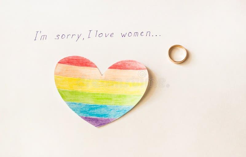 Pierścionek zaręczynowy na białym tle i inskrypcja kocham kobiety, serce w postaci LGBT flaga, lesbian zdjęcie stock