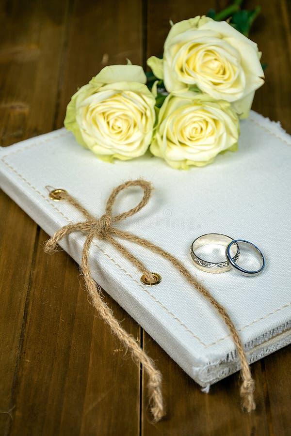 Pierścionki i róże na białej książce fotografia stock
