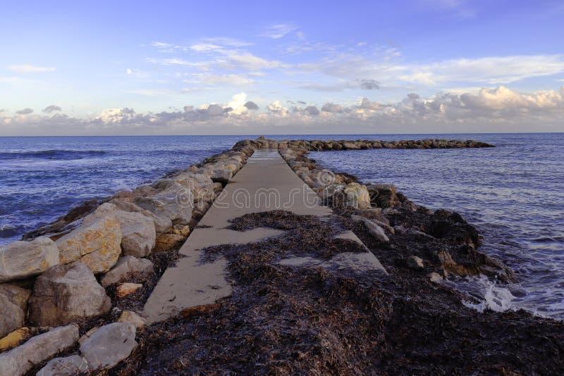 Pier/Anlegestelle von den Felsen bedeckt in der Meerespflanze und im schönen Himmel, Cala-bona, Mallorca, Spanien lizenzfreie stockbilder