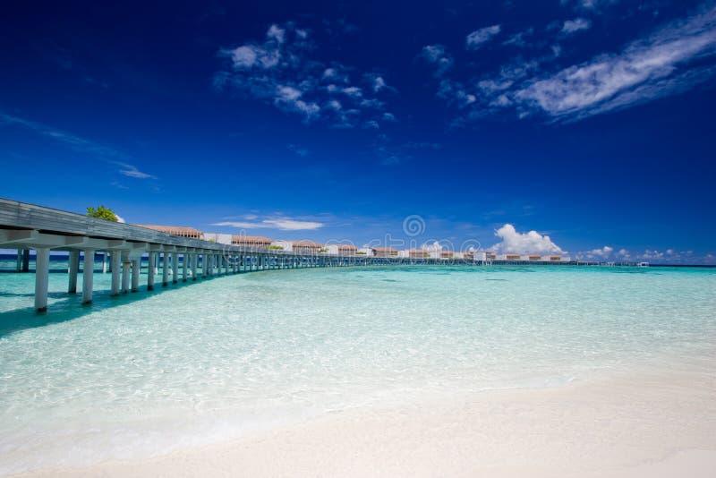 Pier with aqua villas on the horizon royalty free stock photography