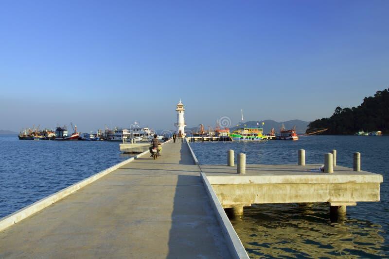 Pier in Bang Bao Bay. Concrete pier with lighthouse and boats docked at the far end in Bang Bao Bay, Ko Chang island, Thailand stock photos
