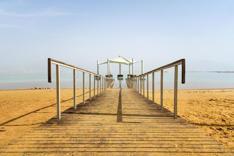 Pier on the beach over Dead Sea. Ein Bokek, Israel. Wooden path on yellow sand leaving in the distance of the dead sea. The path stock photo