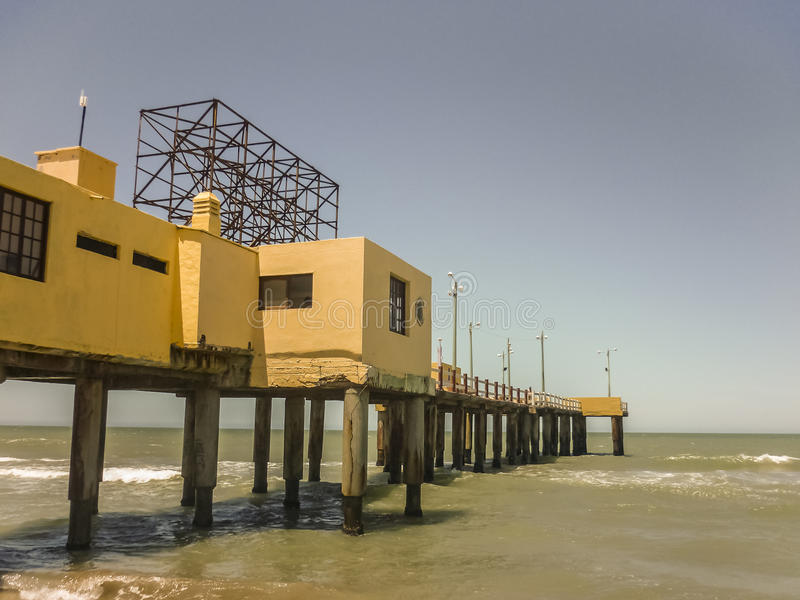 Pier at the Beach in Pinamar Argentina. Yellow construction pier with nobody day scene at the beach in the city of Pinamar, a luxury seaside resort of Argentina royalty free stock image