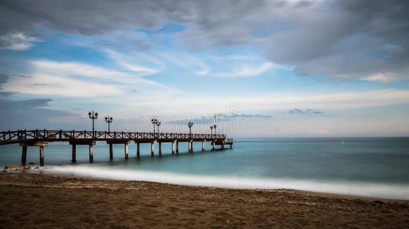 Pier on the beach at sunset. royalty free stock photo