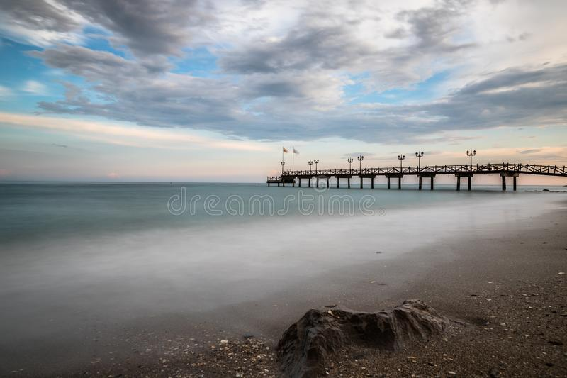 Pier on a beach at sunset. stock images