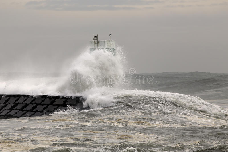 Pier and beacon covered by sea waves. Pier and lighthouse covered by huge oceanic waves. Douro river mouth, Porto, Portugal royalty free stock photo