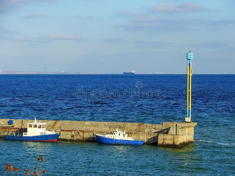 The pier in the blue sea, near which are the boats royalty free stock image